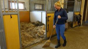 Patricia Westman sopar stallgolvet utanför hästarnas boxar.