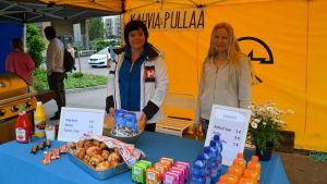 Två kvinnor står inne i ett gult torgtält bakom ett bord med olika drycker och sötsaker till salu.