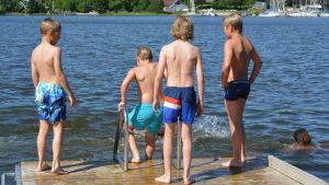 Barn på brygga vid badstrand