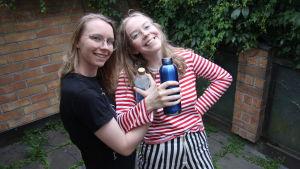 Två tjejer står och ler med vattenflaskor i handen.