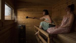Kaksi ihmistä saunoo, toinen heittää juuri vettä kiukaalle.