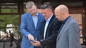 Tre män står och ser på en telefonskärm.
