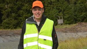 En man med orange keps och gul skyddsväst. Står  ute på en åker som ska bli våtmark.