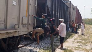 """Människor klättrar ombord på tåget kallat """"La bestia"""" genom Centralamerika  i hopp om att nå USA"""