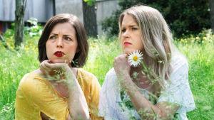 Eva Frantz och Hannah Norrena sitter på en gräsmatta.