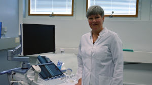 Kvinna står vid en ultraljudsmaskin i ett sjukhus.