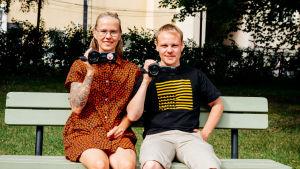 Muuttopäiväkirjat-ohjelman Klaara ja Matti istuvat kesällä puistonpenkillä videokamerat käsissään kohti kameraa.