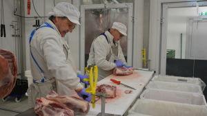 Två slaktare (män) står vid ett bord i ett slakteri och skär och putsar kött.