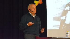 en äldre man föreläser, i bakgrunden syns en del av hans skärm