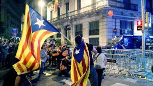 Man invirad i katalansk flagga kastar orangefärgad plastboll mot polis.