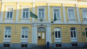En kvinna med rullator går förbi ett stort gammalt gult stadshus.