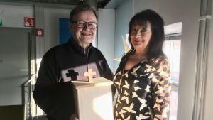 Pekka Saarela håller en urna, tillsammans med Erja Laiho.
