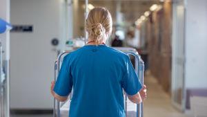 Sjukvårdare går i en sjukhuskorridor.