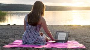 En ung kvinna sitter på stranden med en laptop.