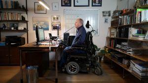En man i elektrisk rullstol sitter framför en datorskärm i kontorsmiljö.