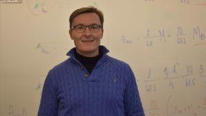 En man med glasögon och blå tröja. Bakom en vit skoltavla med matematiska formler
