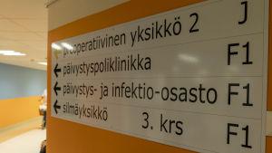 Kyltti keskussairaalan seinällä opastaa infektio-osastolle.