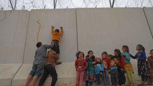 Syriska flyktingbarn klättrar vid en gränsmur som Turkiet byggt mot den syriska byn Kafr Lusin, i Idlib.