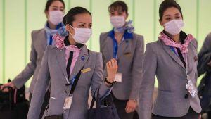 En grupp asiatiska flygvärdinnor med munskydd på flygfältet i Los Angeles.