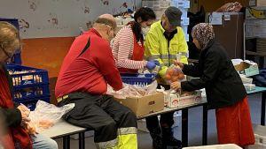 Ett flertal personer i arbetskläder packar ner matvaror i plastpåsar.