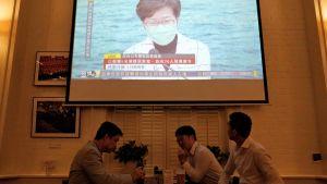 Några män sitter i en bar och dricker öl och ser på en presskonferens på tv.