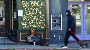 En bostadslös man sitter lutad mot en byggnad på en gata i San Francisco, Kalifornien den 1 april 2020.