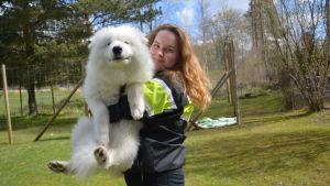 Natalia Mattsson, en flicka med rödbrunt hår har på sig en svart rock med gul-vita ärmar. Natalia Mattsson håller en vit hund i famnen.