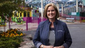 Porträtt av en kvinna i axellång polkafrisyr. Hon tittar in i kameran och ler. I bakgrunden syns nöjesfältet Borgbacken.