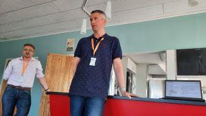 två män står och håller en presentation vid en bardisk i en UF lokal