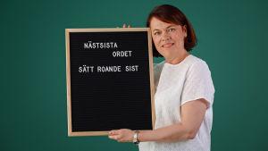"""Martina Harms-Aalto håller i en svart skylt med vit anagrammen: """"Näst sista ordet, sätt roande sist""""."""