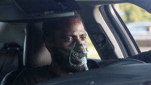 Protagonisten i förarsätet  på en bil iklädd syrgasmask.