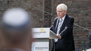 En man i kostym står vid ett podium. Han har vit skjorta och randig slips. Han ser allvarlig ut och han vitt hår och glasögon. I förgrunden till vänster ett huvud som är iklätt en kippa.