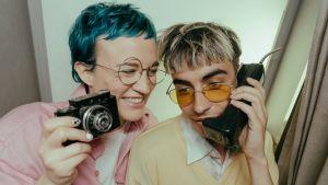 Kaksi nuorta vanhan kännykän ja kameran kanssa