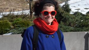 kvinna i röda solglasön och blå kappa