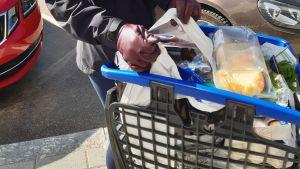 En kundvagn till brädden fylld med livsmedel, kassar och en kvinna som lyfter ut en kasse