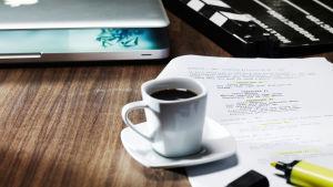 En dator, en kaffekopp, en filmklappa och ett manus.