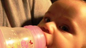 Vauva juo maitoa pullosta.