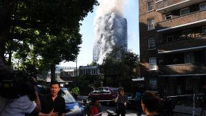 Tjock rök väller ut ur det brinnande 27-våningshuset.