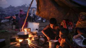 Två barn äter under under en presenning i ett flyktingläger i Ukhiya, Bangladesh, lördagen 16.9.2017.