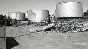 Svartvit bild på tre oljecisterner, en grävmaskin och en hel del skräp.