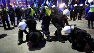 Kravallpoliser arresterar en person.