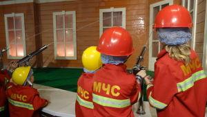 Barn klädda som brandsoldater leker att de släcker en eld