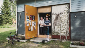 Två personer står vid en öppen dörr.