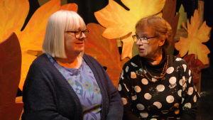 Teateraktiva Skini Lindgård och Ingeborg Spiik sitter i en teaterdekor