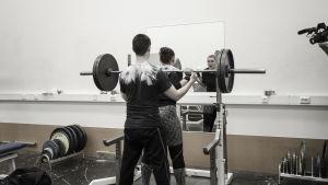 En kvinna och en man i ett gym. Kvinnan har en skivstång på axlarna och mannen står bakom och vaktar så hon inte tappar stången.