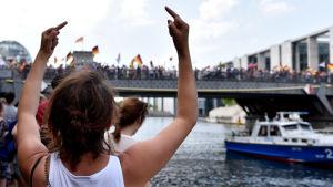 En motdemonstrant visar långfingret åt AfD-demosntrationen i Berlin i maj 2018.