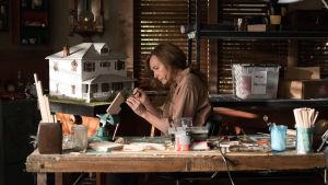 Annie (Toni Colette) sitter och gör miniatyrer vid ett bord.