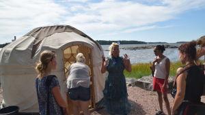 kvinnor framför tält vid strand