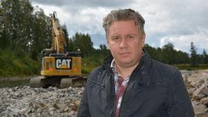 En man som står vid en å bredvid en grävmaskin.