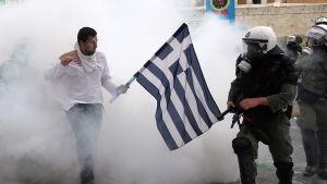 Grekisk man som håller flagga framför kravallpoliser